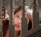 Mujer joven hermosa que mira a escondidas a través de la escalera Fotos de archivo libres de regalías