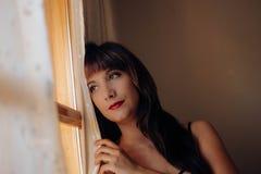 Mujer joven hermosa que mira hacia fuera esperar de la ventana fotografía de archivo