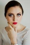 Mujer joven, hermosa que mira la cámara aislada en el backgr blanco Imagen de archivo