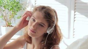 Mujer joven hermosa que mira la cámara mientras que escucha la música en los auriculares almacen de video