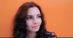 Mujer joven hermosa que mira la cámara y 4K sonriente metrajes
