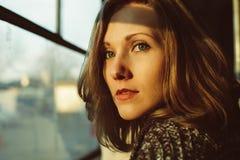 Mujer joven hermosa que mira la ventana durante puesta del sol Foto de archivo libre de regalías