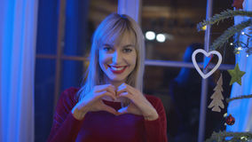 Mujer joven hermosa que muestra símbolo y la sonrisa del corazón Foto de archivo libre de regalías