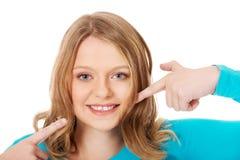 Mujer joven hermosa que muestra sus dientes Fotografía de archivo libre de regalías