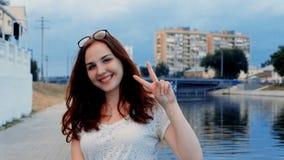 Mujer joven hermosa que muestra V con los fingeres para la victoria almacen de metraje de vídeo