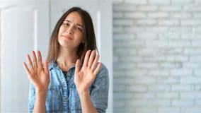 Mujer joven hermosa que niega la oferta, haciendo gesto de la parada con sus manos, mirando la cámara almacen de video