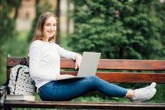 Mujer joven hermosa que pone en banco y que trabaja en el ordenador portátil al aire libre Foto de archivo libre de regalías