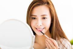 Mujer joven hermosa que pone en el lápiz labial rojo Imagen de archivo libre de regalías