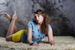 Mujer joven hermosa que pone en el piso blanco Imagen de archivo