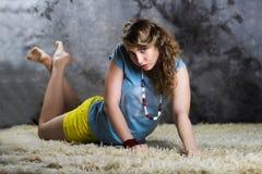 Mujer joven hermosa que pone en el piso blanco Fotografía de archivo libre de regalías