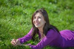 Mujer joven hermosa que pone en hierba Imagenes de archivo