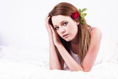 Mujer joven hermosa que presenta con la flor color de rosa en pelo y que miente en cama imagenes de archivo