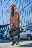 Mujer joven hermosa que presenta con un bolso de cuero en un vestido Imagen de archivo libre de regalías