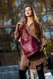 Mujer joven hermosa que presenta con un bolso de cuero en un vestido Imágenes de archivo libres de regalías