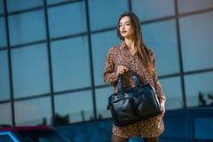 Mujer joven hermosa que presenta con un bolso de cuero en un vestido Fotografía de archivo