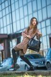Mujer joven hermosa que presenta con un bolso de cuero en un vestido Imagen de archivo