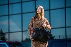 Mujer joven hermosa que presenta con un bolso de cuero en un vestido Foto de archivo