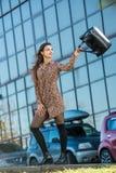 Mujer joven hermosa que presenta con un bolso de cuero en un vestido Fotos de archivo libres de regalías