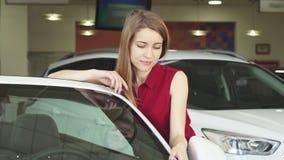 Mujer joven hermosa que presenta con un nuevo auto en la representación almacen de metraje de vídeo