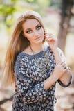 Mujer joven hermosa que presenta en un bosque del otoño Imágenes de archivo libres de regalías