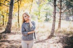 Mujer joven hermosa que presenta en un bosque del otoño Fotografía de archivo