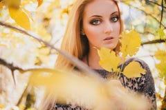 Mujer joven hermosa que presenta en un bosque del otoño Imagenes de archivo