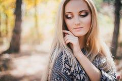 Mujer joven hermosa que presenta en un bosque del otoño Foto de archivo libre de regalías