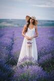 Mujer joven hermosa que presenta en un campo de la lavanda fotos de archivo