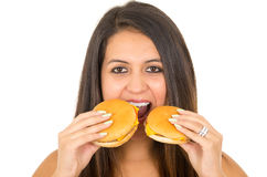 Mujer joven hermosa que presenta para la cámara que sostiene dos hamburguesas al lado de boca, sonriendo feliz, fondo blanco del  Imagen de archivo