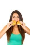 Mujer joven hermosa que presenta para la cámara que sostiene dos hamburguesas al lado de boca, sonriendo feliz, fondo blanco del  Fotografía de archivo
