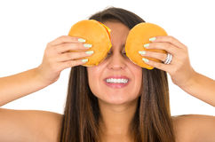 Mujer joven hermosa que presenta para la cámara que sostiene dos hamburguesas delante de ojos, sonriendo feliz, estudio blanco Fotografía de archivo libre de regalías