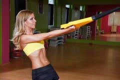 Mujer joven hermosa que presenta un ejercicio de TRX Fotografía de archivo libre de regalías