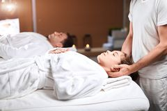 Mujer joven hermosa que recibe masaje en la zona principal y de los hombros en centro del balneario foto de archivo libre de regalías