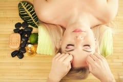 Mujer joven hermosa que recibe masaje facial en un salón del balneario imagen de archivo