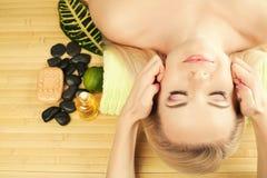 Mujer joven hermosa que recibe masaje facial en un salón del balneario Imagenes de archivo