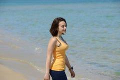 Mujer joven hermosa que recorre en la playa foto de archivo