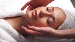 Mujer joven hermosa que relaja el balneario facial de recepción femenino de la belleza del masaje del cuerpo metrajes