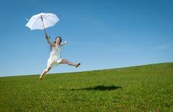 Mujer joven hermosa que salta con el paraguas blanco Fotografía de archivo libre de regalías