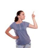 Mujer joven hermosa que señala y que mira a la izquierda Fotos de archivo libres de regalías