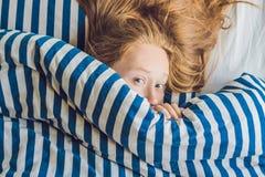 Mujer joven hermosa que se acuesta en cama y dormir No consiga bastante concepto del sueño fotografía de archivo