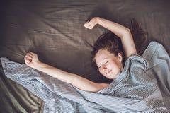 Mujer joven hermosa que se acuesta en cama y que duerme, visión superior No consiga bastante concepto del sueño Foto de archivo