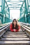 Mujer joven hermosa que se acuesta en las vías del tren fotografía de archivo