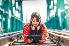 Mujer joven hermosa que se acuesta en v?as del tren usando la tableta de Digitaces foto de archivo libre de regalías