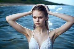 Mujer joven hermosa que se baña en el mar en un traje de baño, vacaciones, playa, sol, verano Fotografía de archivo