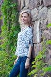 Mujer joven hermosa que se coloca cerca de una pared de piedra Fotos de archivo