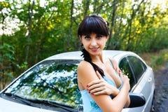 Mujer joven hermosa que se coloca en el camino cerca del coche imagen de archivo libre de regalías