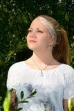 Mujer joven hermosa que se coloca en el verdor Imagen de archivo