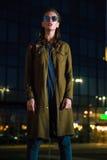 Mujer joven hermosa que se coloca en la calle iluminada en la noche Fotografía de archivo libre de regalías