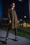 Mujer joven hermosa que se coloca en la calle iluminada en la noche Fotos de archivo libres de regalías