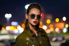 Mujer joven hermosa que se coloca en la calle iluminada en la noche Imagen de archivo
